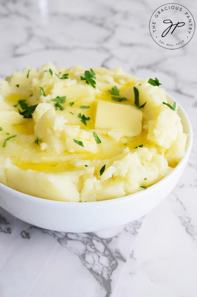 A side view of of Instant Pot mashed potatoes with melted butter on them.