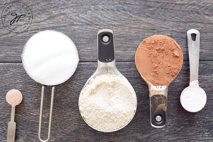 Mug cake mix ingredients lined up in their measuring cups and spoons.