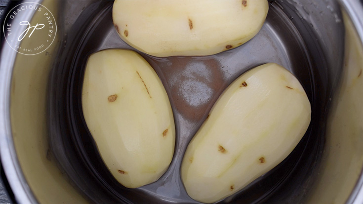 Three large potatoes in the Instant Pot with water and salt.