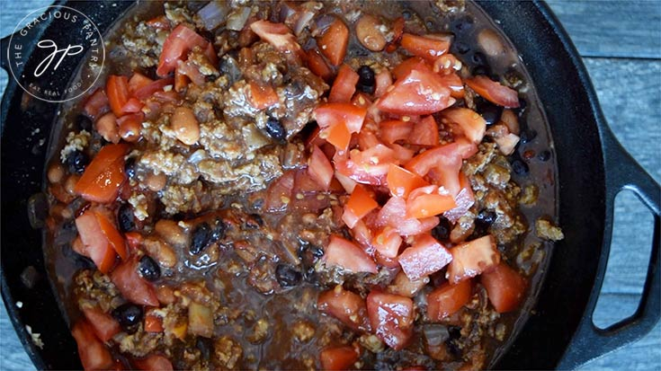 Adding the remaining ingredients and simmering.