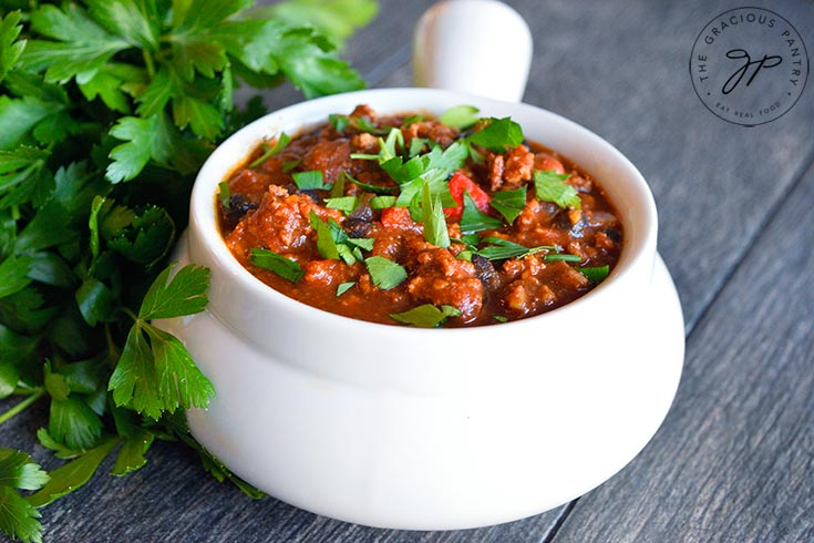 Horizontal shot of a white crock filled with turkey chili and garnished with chopped parsley.