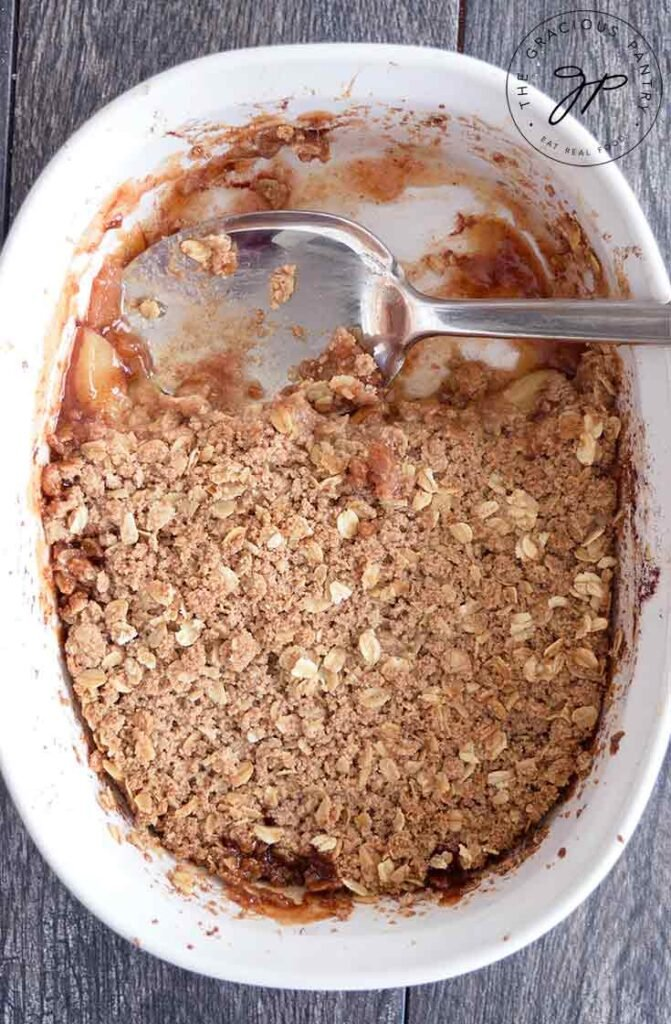 A casserole dish with apple crisp that has been partially scooped out.