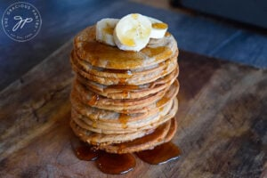A horizontal side view of this Banana Pancakes Recipe. A stack of banana pancakes sits on a cutting board, topped with banana slices and maple syrup which is dripping down the sides onto the board.