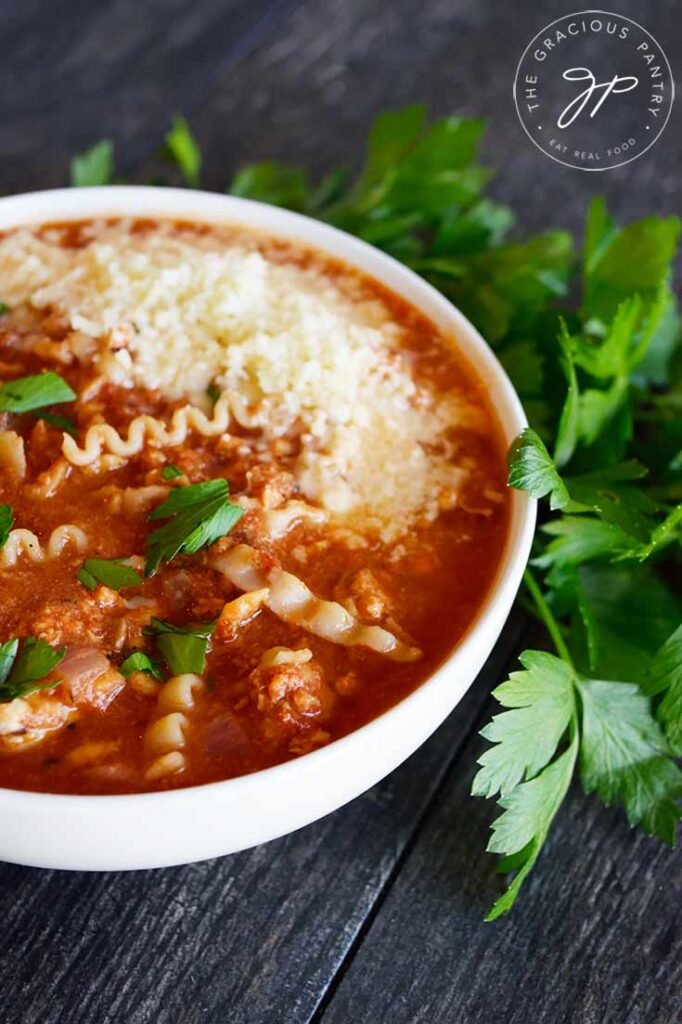 Side view of a white bowl filled with this Lasagna Soup Recipe.