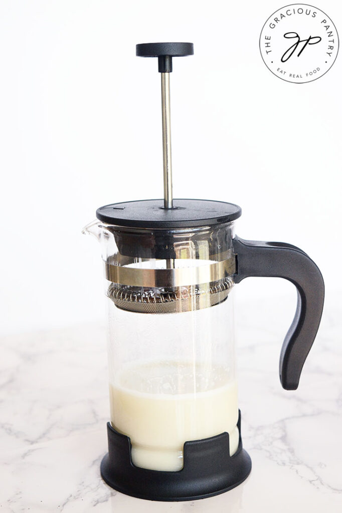 Milk in a french press ready to be frothed to make this London Fog Recipe.