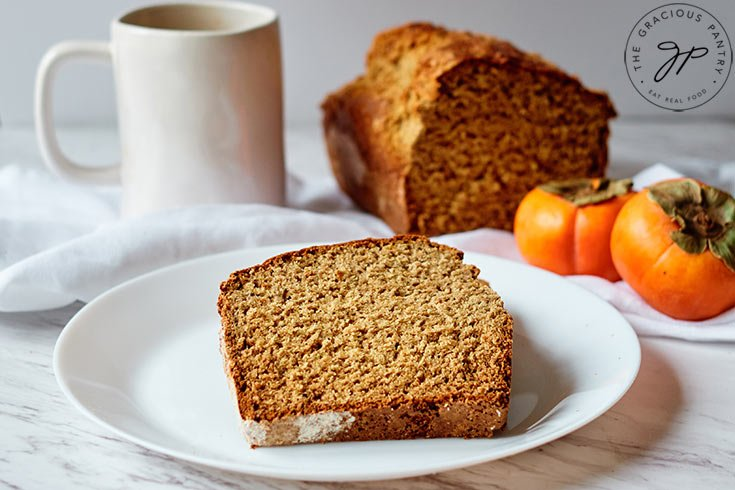 A plate with a slice of Persimmon Bread just cut from the loaf that sits behind it.