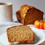 A slice of persimmon bread served on a plate. The cut loaf sits behind it and a mug sits at the back to the left.