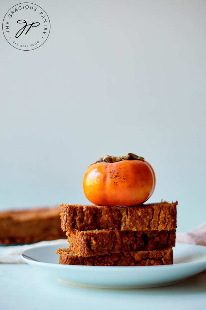 Three thick slices of persimmon bread are stacked on a plate with a persimmon sitting on top.
