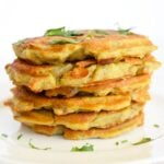 A stack of these potato pancakes sit stacked on a white plate.