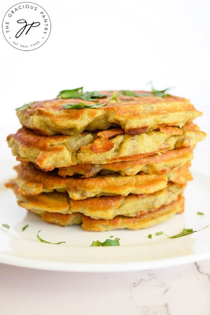 A stack of these potato pancakes sit stacked on a white plate made with this potato pancake recipe.
