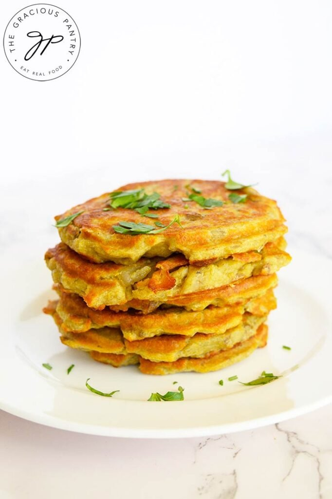 Side view of a stack of potato pancakes with fresh parsley for garnish.