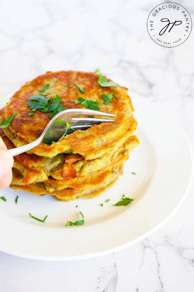 A fork pressing into these potato pancakes in this potato pancake recipe.
