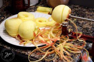 Apples being peeled on the apple peeler.
