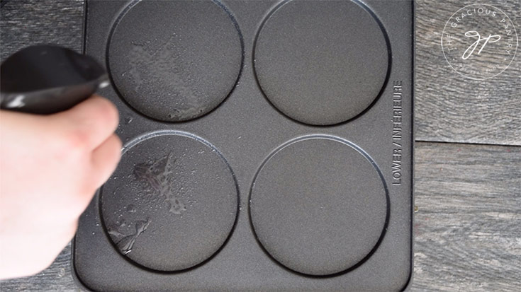 Spraying oil on the pan.