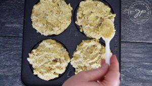 Spreading potato batter into pancakes on the pan.