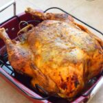 A roasted Thanksgiving turkey cooling in a roasting pan.