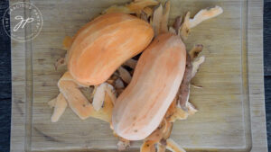 Two sweet potatoes lay on a bed of their peels.
