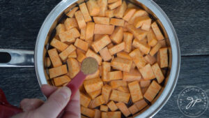 A pot with chopped sweet potatoes, chicken broth and nutmeg being added.