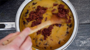Stirring cooked bacon into the pot of Bacon Sweet Potato Soup.