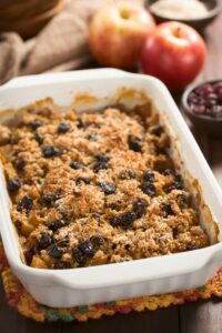 A white casserole dish sits on a table filled with a baked oatmeal recipe.