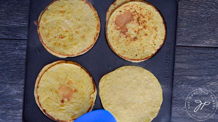 The pancakes cooking on the griddle.