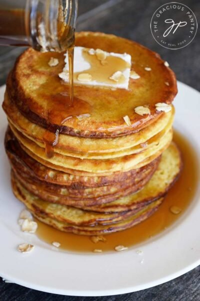 A stack of oat pancakes with maple syrup being poured over the top.