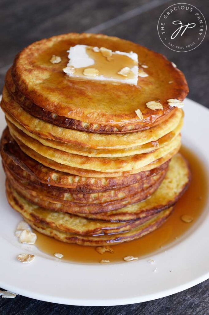 A stack of warm, oat pancakes on a white plate on a dark background. Butter and maple syrup top the pancakes.