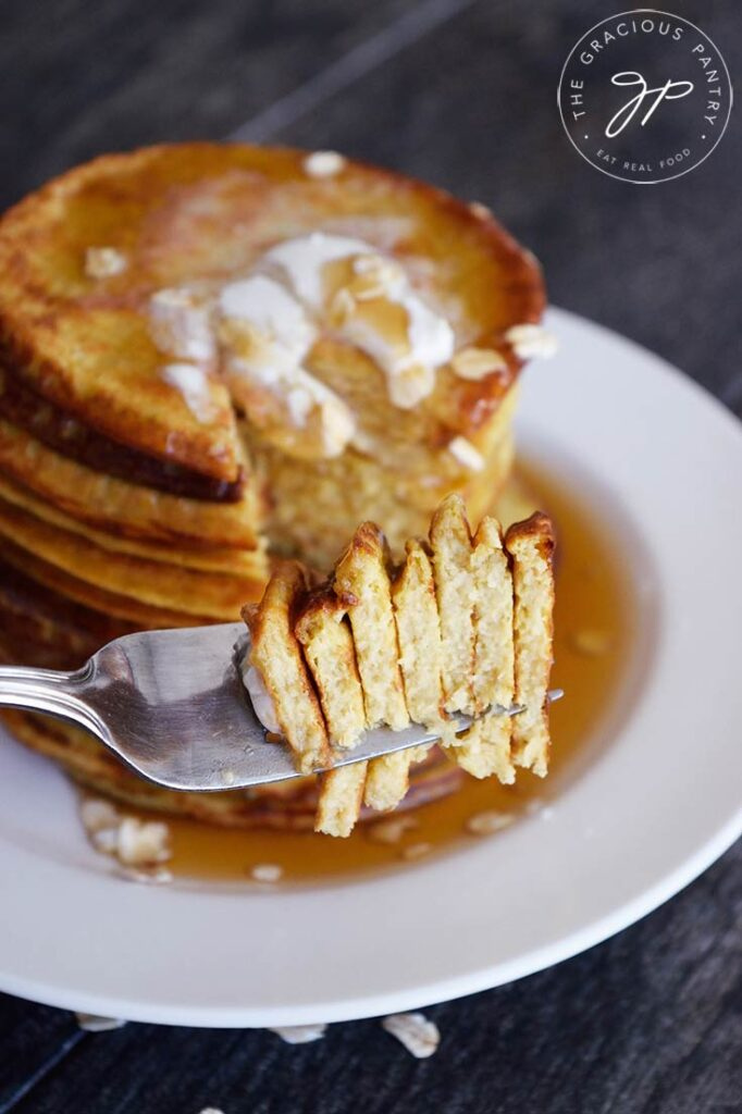 A stack of oat pancakes sits in the background of a fork, holding pancake pieces.