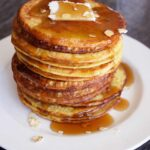 A stack of oat pancakes on a white plate, topped with a pat of butter and plenty of maple syrup.