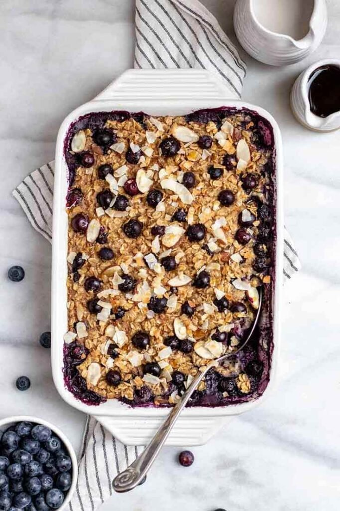 A white casserole dish sits on a table, filled with this blueberry baked oatmeal recipe.