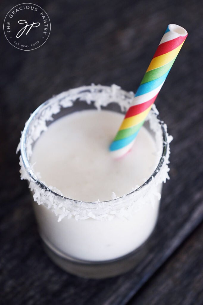 A coconut milk smoothie in a shot glass with a rainbow straw and coconut shreds around the rim of the glass.