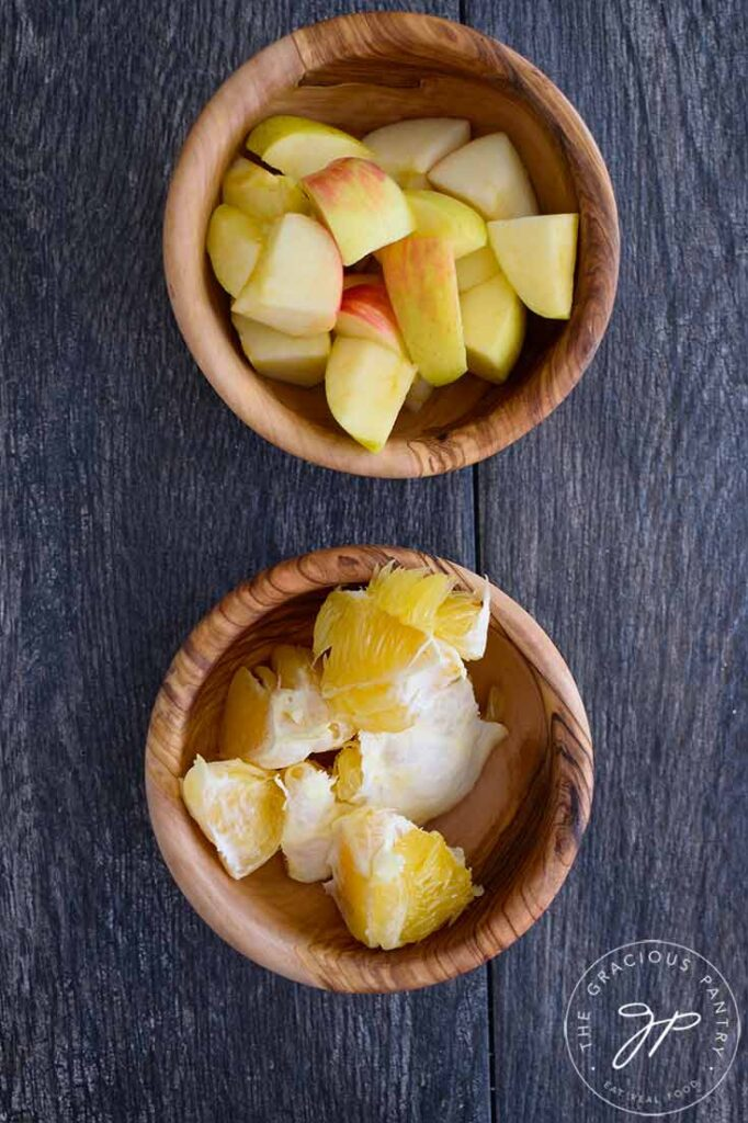 Two wooden bowls, one filled with chopped apples, the other filled with chopped oranges, for making cranberry relish.