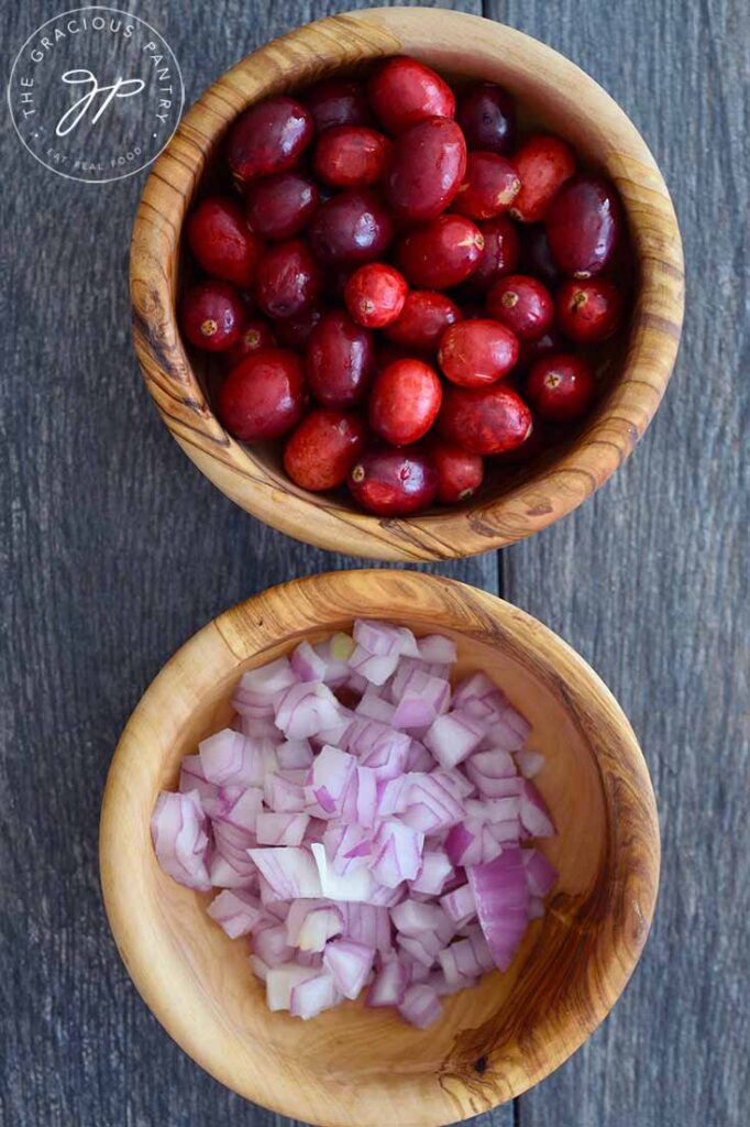 Two wooden bowls, one filled with fresh cranberries, and the other with chopped red onions. Both ingredients are used in making this cranberry relish.