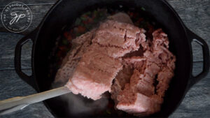 Adding ground meat to the dutch oven for this Dutch Oven Chili Recipe.