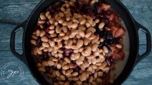 Adding canned pinto beans to the dutch oven for this Dutch Oven Chili Recipe