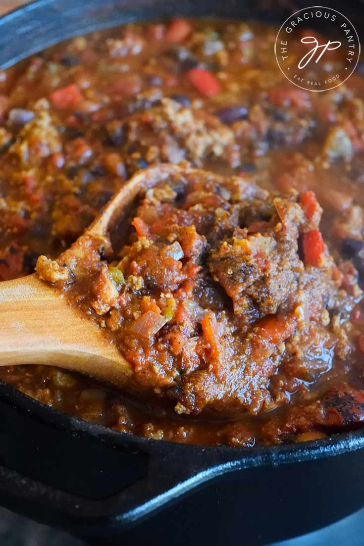 The finished Dutch Oven Chili Recipe being scooped out of the dutch oven for serving.