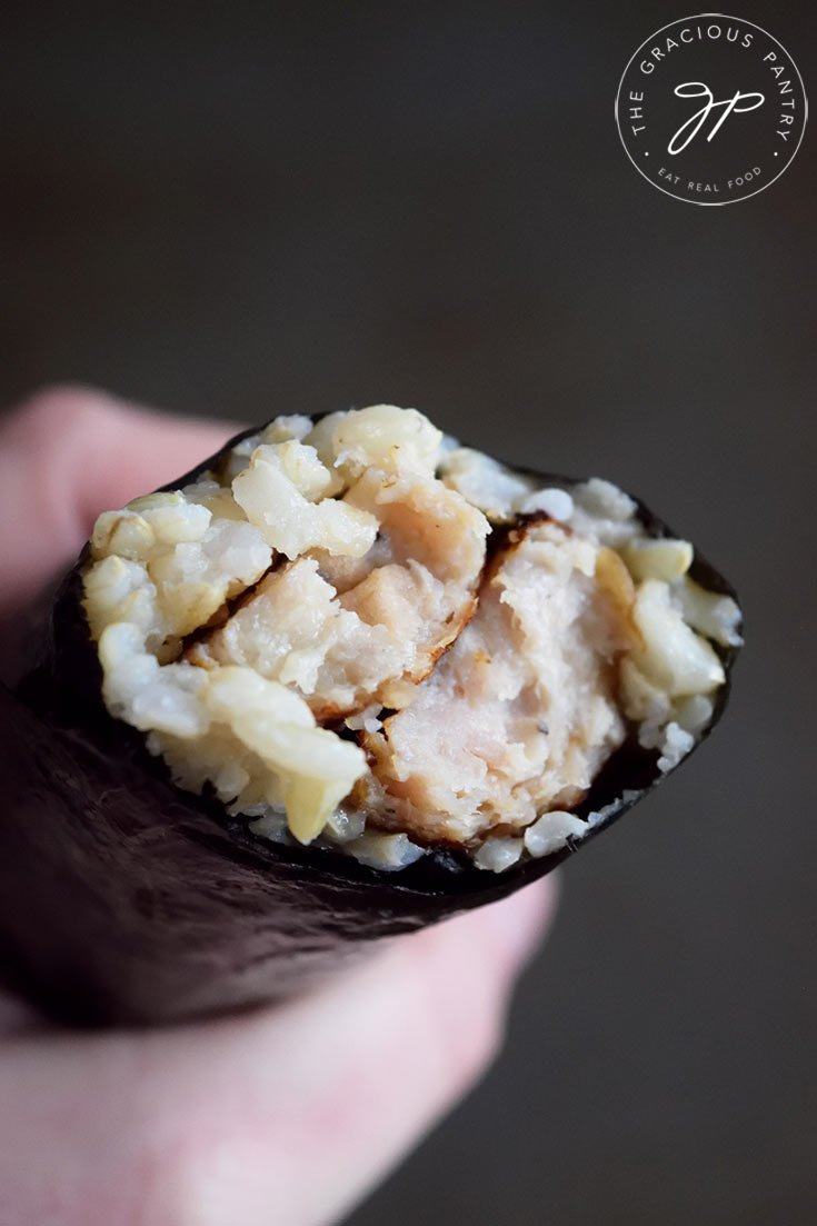 A roll of Gimbap with a bite taken off. You can see the sausage and rice inside the nori.