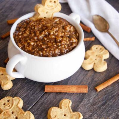 A bowl of gingerbread oatmeal sits on a table surrounded by gingerbread man cookies and cinnamon sticks.