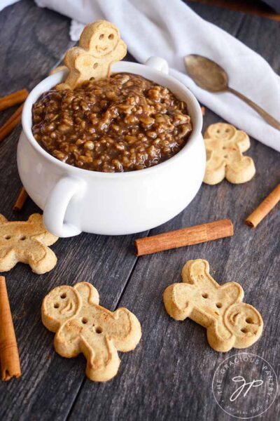 Gingerbread man cookies lay scattered around a while crock filled with gingerbread oatmeal.