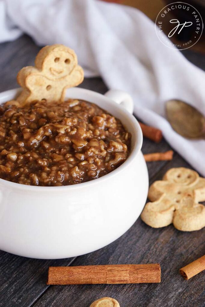 A side view of a white bowl filled with gingerbread oatmeal. Cinnamon sticks and cookies are scattered around the bowl.