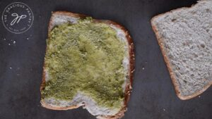 Pesto smeared on a slice of flatted bread. Pesto is optional in this recipe.