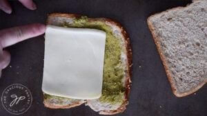 Lining the slice of cheese up with the bottom of the slice of bread.