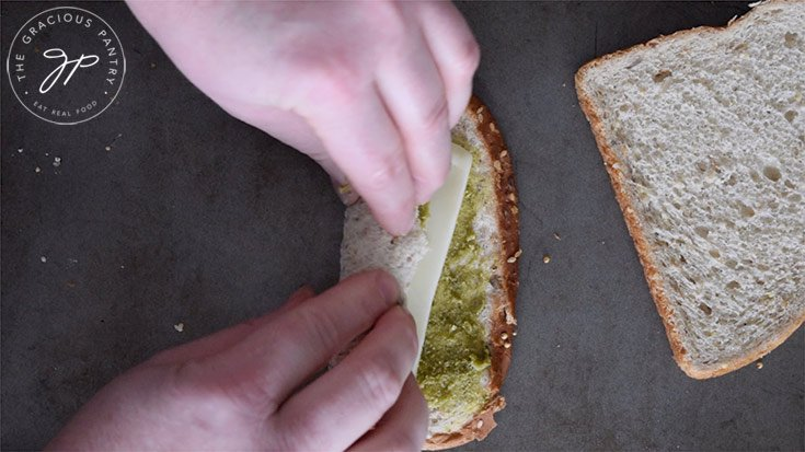 Rolling up the slice of bread with cheese like a rug.