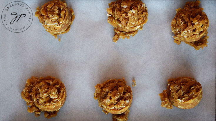 Scoops of Peanut Butter Oatmeal Cookie dough on a cookie sheet.