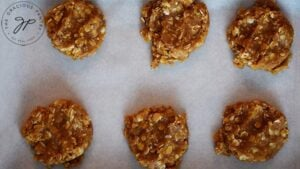 Flattened Peanut Butter Oatmeal Cookie dough scoops on a cookie sheet.