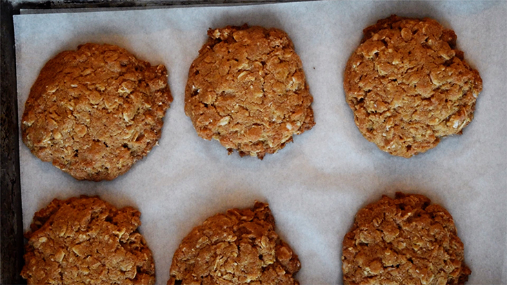 Hot, out of the oven, Peanut Butter Oatmeal Cookies on a cookie sheet.