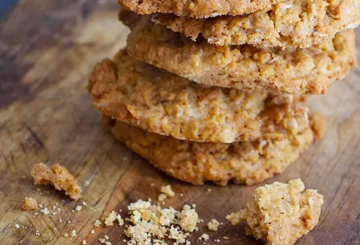 A stack of these Peanut Butter Oatmeal Cookies sit on a cutting board with a few broken pieces sitting in front of the stack.