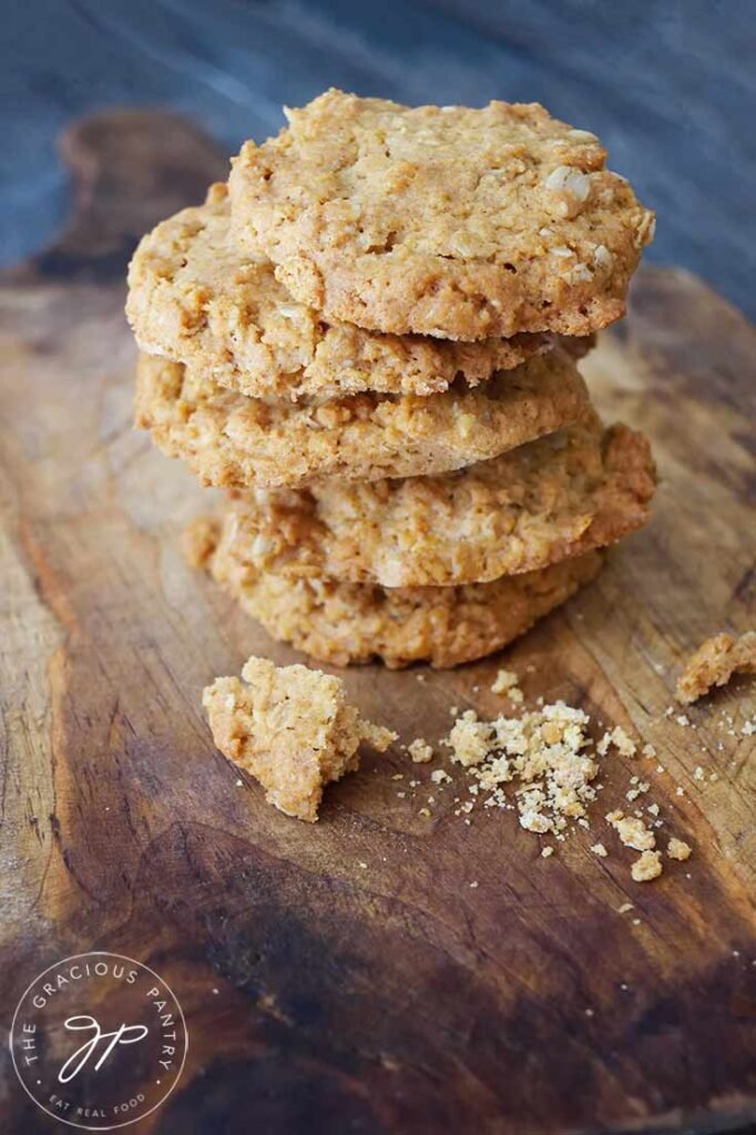 A stack of five Peanut Butter Oatmeal Cookies sit on a wooden cutting board.