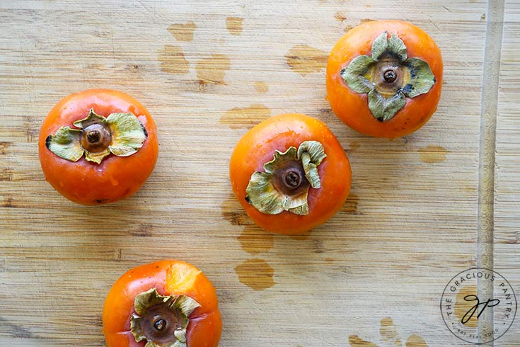 Four whole persimmons sitting on a cutting board about to be made into persimmon pulp.