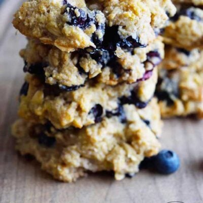 A stack of four blueberry breakfast cookies on a cutting board. You can see blueberries throughout the cookies.